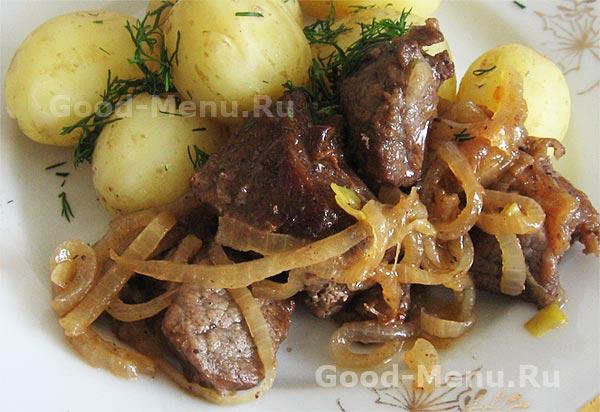 жареная говядина с луком и морковью на сковороде
